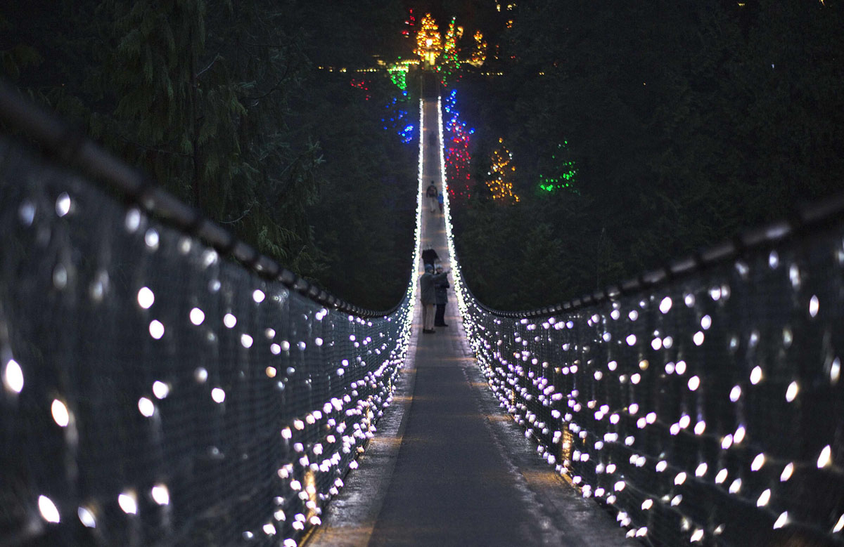 Visitors walk across the Capilano Suspension Bridge decorated in Christmas lights in North Vancouver, British Columbia December 10, 2012. Originally built in 1889, the bridge stretches 135 metres across and 70 metres above the Capilano River.REUTERS/Andy Clark (CANADA - Tags: SOCIETY) ORG XMIT: AXC04